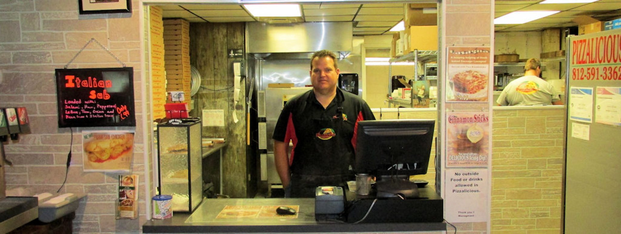 Owner William Brewer standing behind counter